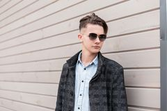 Handsome young hipster man with trendy hairstyle in dark sunglasses in a stylish plaid jacket in shirt poses on the street. Near a wooden wall in the city. Nice stock images