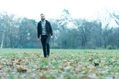 Hipster man walking in the park stock images