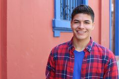 Handsome young hispanic male smiling outdoors.  stock photo