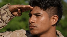 Enlisted Male Soldier Saluting. A handsome young Hispanic male teen Stock Photo