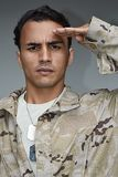 Male Soldier Saluting. A handsome young hispanic man Stock Image