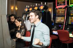 Excited man winning in a slot machine. Handsome young Hispanic men looking excited and celebrating after hitting the jackpot in a slot machine at a casino Stock Image