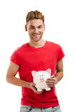 Some savings for my studies. Handsome young holding a piggybank and smiling, isolated over a white background Royalty Free Stock Photo