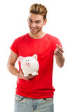 Some savings for my studies. Handsome young holding a piggybank and smiling, isolated over a white background Stock Image