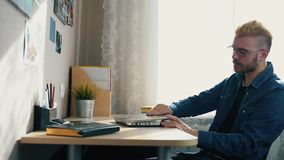 Handsome young home freelancer with glasses and yellow hair working at home, using a laptop. While Getting Bad News from stock video footage