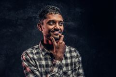 Handsome young Indian guy wearing a checkered shirt holding hand on chin and looking sideways with a pensive look royalty free stock photos