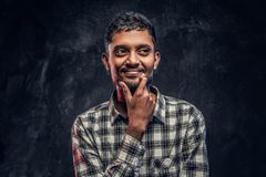 Handsome young Indian guy wearing a checkered shirt holding hand on chin and looking sideways with a pensive look royalty free stock images