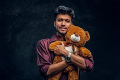 Handsome young Indian man in stylish shirt hugs teddy bear and looking at a camera. royalty free stock image