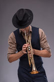 Handsome young jazz man. Waist-up portrait of a jazz man in a suit with a black hat hiding his face and playing a trumpet isolated on grey background with copy Stock Image