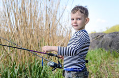 Handsome Young Kid Holding his Fishing Rod Royalty Free Stock Photography