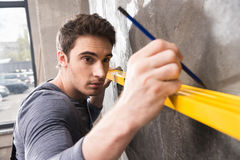 Handsome young laborer with pencil measuring wall with level tool. Renovation concept Royalty Free Stock Photos