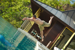 Handsome young lifeguard plunge in swimming pool to rescue. Professional guard at work royalty free stock images