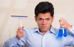 Handsome young mad man holding a cleaning spray bottle in one hand and a window cleaner in his other hand.  Stock Image