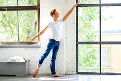 A handsome young male Ballet dancer practicing in a Loft style A. Partment Stock Image