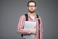 Handsome and young Male college student carrying bag on white background while holding college laptop isolated on gray. Handsome and young indian Male college Royalty Free Stock Images