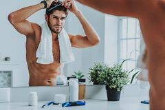 Handsome young male comb his hair in morning stock images