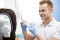 Handsome young male dentist demonstrating teeth mold. Your dentist. Professional male dentist smiling talking to his client showing a dental mold healthcare royalty free stock photo