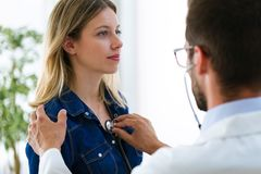 Handsome young male doctor checking beautiful young woman patient heartbeat using stethoscope in medical office. Shot of handsome young male doctor checking royalty free stock photos