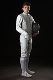 Handsome Young male fencer in white fencing costume. Portrait of Handsome Young male fencer in white fencing costume against Dark Background royalty free stock photography