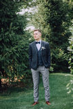 A handsome young male groom in a three-piece suit and a bow-tie stands on a lawn against a spruce Royalty Free Stock Photo