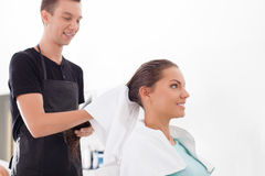 Handsome young male hairdresser is serving his Royalty Free Stock Photos