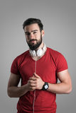 Handsome young male with headphones in red t-shirt looking at camera Stock Photography