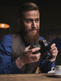 Handsome young male journalist is making shots. Let me photograph you. Attractive bearded photographer is holding a camera and smiling. He is sitting at the Royalty Free Stock Images