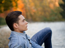 Handsome young male model on pond or lake in fall Royalty Free Stock Photography
