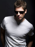Handsome young male model with sunglasses. Handsome young male model in a white t-shirt with sunglasses Royalty Free Stock Photos