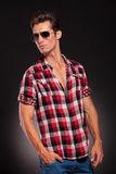 Handsome young male model  with sunglasses. Studio side view of a handsome young male model wearing jeans , shirt and sunglasses Stock Photography