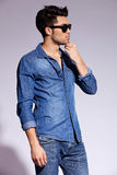 Handsome young male model wearing jeans shirt. Studio side view of a handsome young male model wearing jeans shirt and sunglasses Royalty Free Stock Image