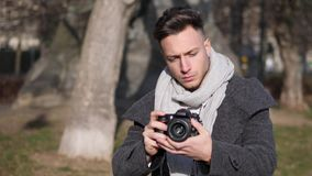 Handsome young male photographer filming video footage outside. Handsome young male photographer or videomaker filming video footage with professional stock footage
