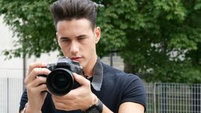 Handsome young male photographer taking photograph Stock Photos