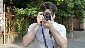 Handsome young male photographer taking photograph Royalty Free Stock Photo
