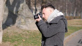 Handsome young male photographer taking photograph outside. Handsome young male photographer taking photograph with professional photo camera, outdoor in city stock video