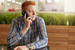 A handsome young male with red hair dressed in checked shirt sitting at wooden table in the restaurant isolated over greenery talk Stock Photo