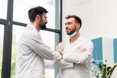 Handsome young male scientists in white coats talking and smiling each other in chemical lab royalty free stock photography