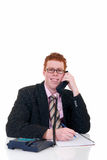Handsome young male secretary. Handsome red-headed smiling young male secretary, help desk assistant making phone call. White background, studio shot Royalty Free Stock Images