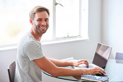 Handsome young male student smiling at camera seated behind laptop Royalty Free Stock Images