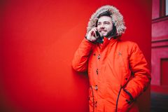 Handsome young male student with a toothy smile and a beard stands on a red wall background in a bright red winter jacket with a h. Ood with fur in winter. Uses Royalty Free Stock Photos