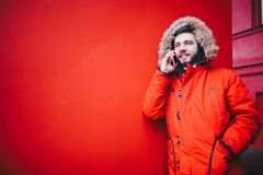 Handsome young male student with a toothy smile and a beard stands on a red wall background in a bright red winter jacket with a h. Ood with fur in winter. Uses Royalty Free Stock Images
