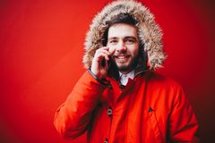 Handsome young male student with a toothy smile and a beard stands on a red wall background in a bright red winter jacket with a h. Ood with fur in winter. Uses Stock Photo