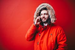 Handsome young male student with a toothy smile and a beard stands on a red wall background in a bright red winter jacket with a h. Ood with fur in winter. Uses Stock Photos