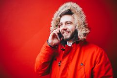 Handsome young male student with a toothy smile and a beard stands on a red wall background in a bright red winter jacket with a h. Ood with fur in winter. Uses Royalty Free Stock Image