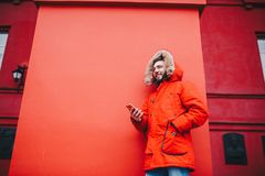 Handsome young male student with toothy smile and beard stands on red wall background in bright red winter jacket with hood with f. Ur, Uses, holds mobile phone Royalty Free Stock Image