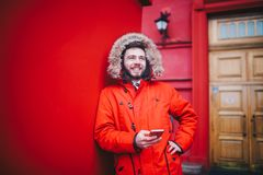 Handsome young male student with toothy smile and beard stands on red wall background in bright red winter jacket with hood with f. Ur, Uses, holds mobile phone Stock Images