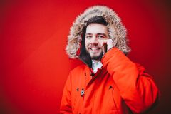 Handsome young male student with a toothy smile and a beard stands on a red wall background in a bright red winter jacket with a h. Ood with fur in winter. Uses Stock Images