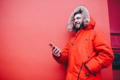 Handsome young male student with toothy smile and beard stands on red wall background in bright red winter jacket with hood with f. Ur, Uses, holds mobile phone Royalty Free Stock Photography