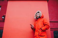 Handsome young male student with toothy smile and beard stands on red wall background in bright red winter jacket with hood with f. Ur, Uses, holds mobile phone Stock Photography