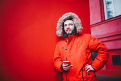 Handsome young male student with toothy smile and beard stands on red wall background in bright red winter jacket with hood with f. Ur, Uses, holds mobile phone Royalty Free Stock Images